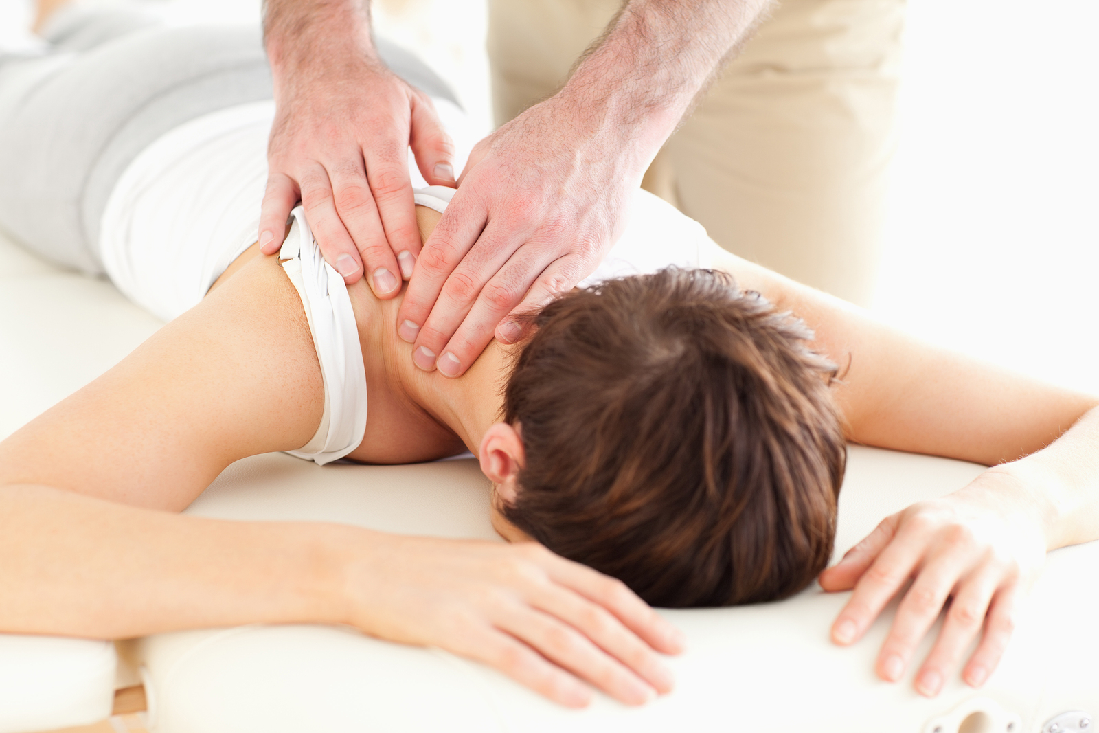chiropractor massaging patients neck